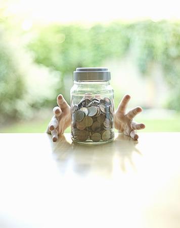 defended: Hands grabbing jar of change