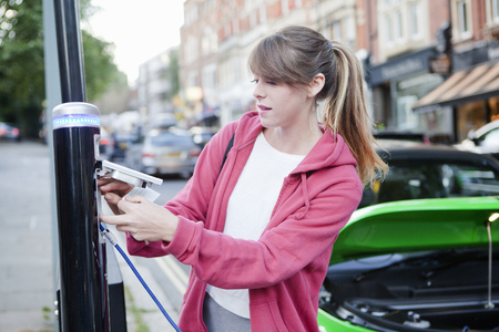 plugging: Woman charging electric car on street LANG_EVOIMAGES