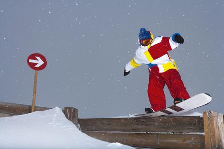 exhilarating: Snowboarder sliding on wooden fence