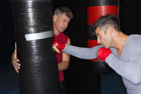 aggressively: Boxer working with trainer in gym LANG_EVOIMAGES