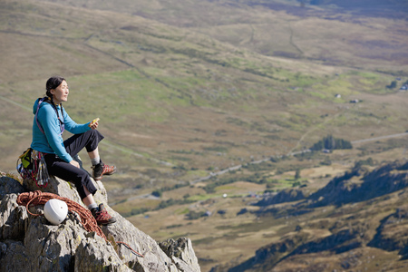 climbed: Female rock climber sitting on a ledge having a break
