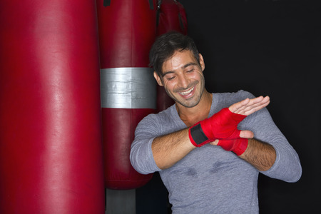 aggressively: Boxer wrapping his hands in gym