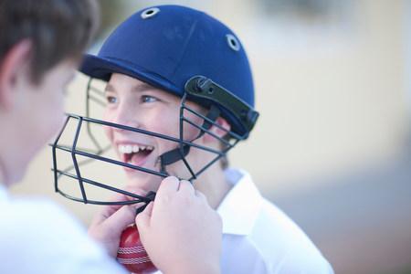 off shoulder: Boy putting cricket helmet on another boy