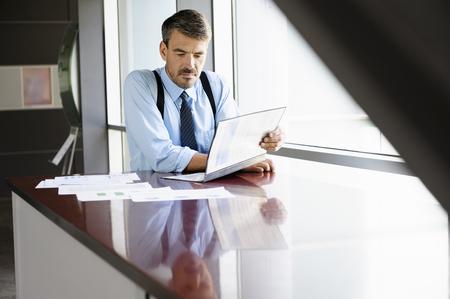 Businessman reading at desk LANG_EVOIMAGES