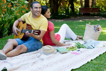 pleasurable: Young couple sitting on picnic blanket,man playing guitar LANG_EVOIMAGES