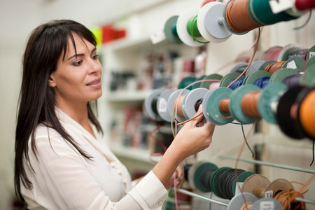 decide deciding: Woman looking at spools of thread in store LANG_EVOIMAGES