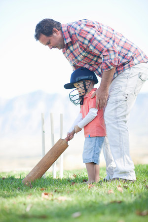 Father and son playing cricket LANG_EVOIMAGES