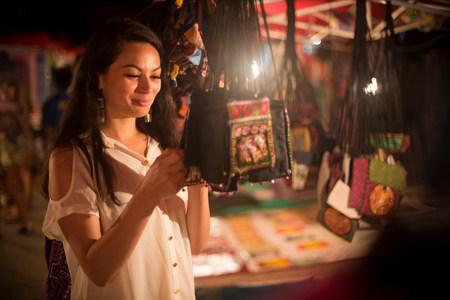 materialism: Woman looking at handbags in night market,Luang Prabang,Laos