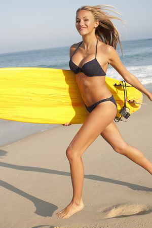 rejoices: Woman carrying surfboard on beach