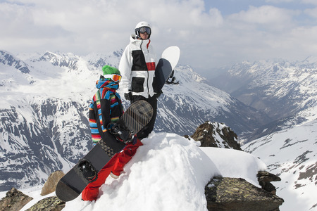 Snowboarders on rocky mountaintop