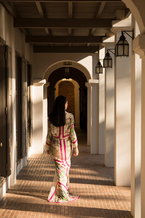 shadowed: Woman walking past columns in hotel