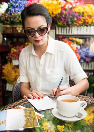 tea breaks: Woman writing postcard in cafe LANG_EVOIMAGES