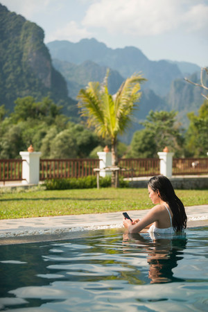 Woman using smartphone in  swimming pool LANG_EVOIMAGES