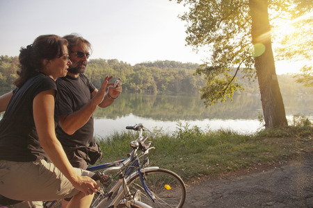 sweethearts: Couple riding bicycles by river bank