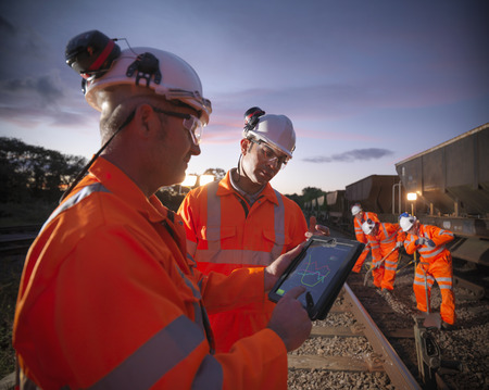 Railway workers using tablet computer LANG_EVOIMAGES