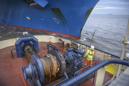safe water: Tugboat worker catching rope on deck LANG_EVOIMAGES