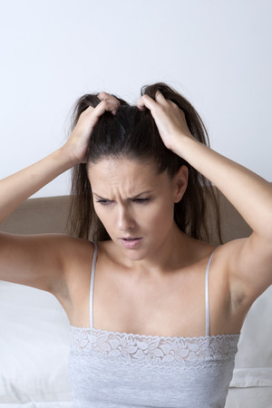 struggled: Woman scratching her head in bed