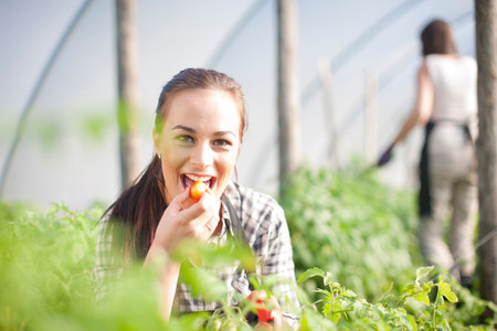 farmyards: Young woman trying produce at vegetable farm