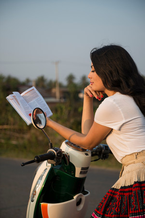 Woman leaning on moped reading book