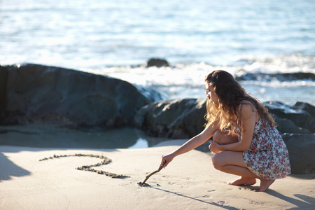 interrogations: Woman drawing question mark in sand