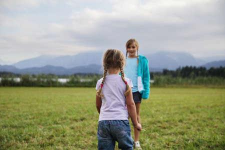 preadolescent: Girls playing in grassy field