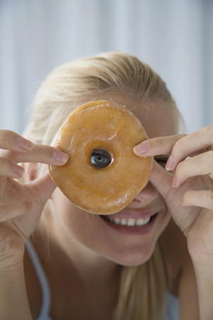 peep: Woman peering through donut hole