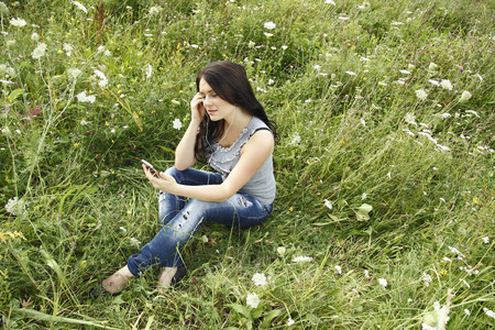 responding: Woman listening to headphones in grass LANG_EVOIMAGES