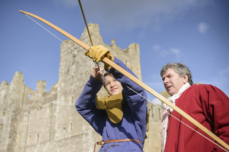 sightseers: Student in period dress shooting arrow