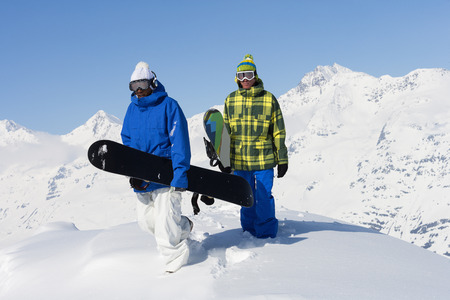 Snowboarders on snowy mountaintop LANG_EVOIMAGES
