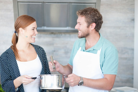 close up food: Young man and woman cooking in kitchen LANG_EVOIMAGES