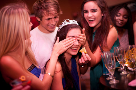 giggling: Young women playing drinking game at hen party