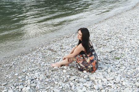 daydream: Woman sitting on rocky beach LANG_EVOIMAGES