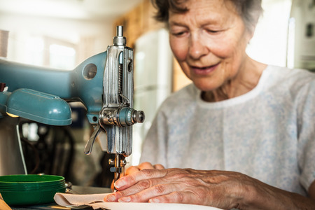 antiquity: Older woman working on sewing machine LANG_EVOIMAGES