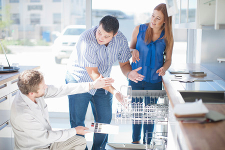 salespeople: Couple and salesman looking at dishwasher in kitchen showroom LANG_EVOIMAGES