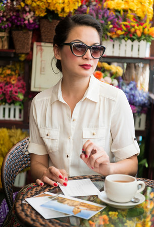 bi: Woman with postcards in cafe