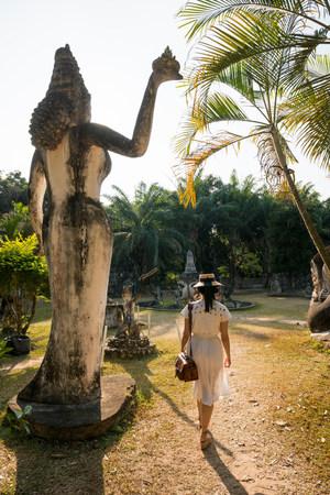 bi: Woman walking past statue,Xieng Khu,Vientiane,Laos LANG_EVOIMAGES