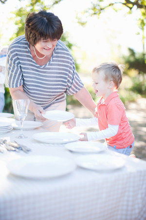 cultivating: Boy and grandmother setting dinner table outdoors