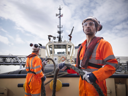 Tugboat worker holding rope on deck