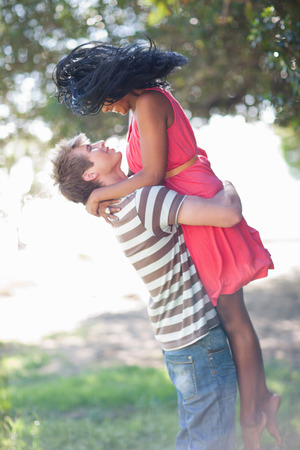 arms lifted up: Man lifting girlfriend outdoors