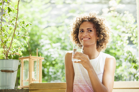 gratify: Smiling woman drinking glass of water