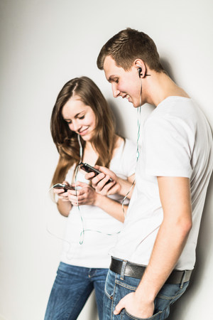 ear buds: Teenage couple leaning against wall listening to mp3 player LANG_EVOIMAGES