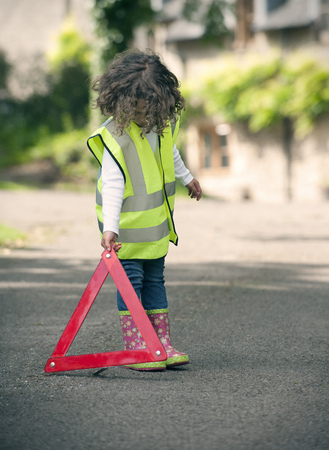 warned: Girl playing traffic worker on rural road
