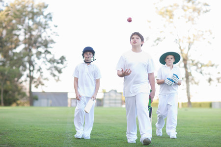 age 10 12 years: Three boys walking on cricket pitch LANG_EVOIMAGES