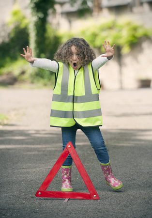 somber: Girl playing traffic worker on rural road