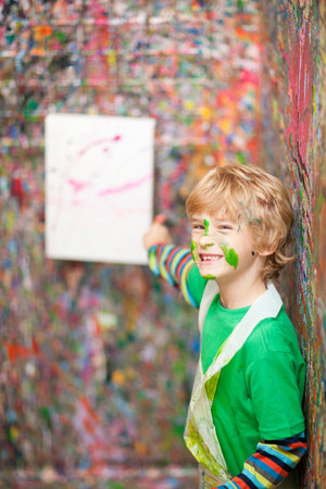 Boy pointing to painting on paint-splattered wall LANG_EVOIMAGES