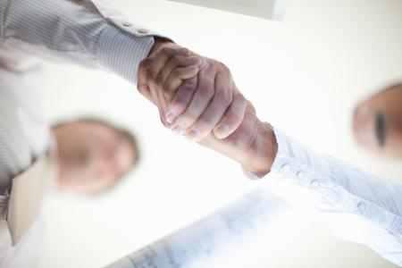 Close up of businessmen shaking hands LANG_EVOIMAGES