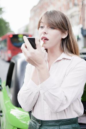in vain: Woman applying lipstick on city street