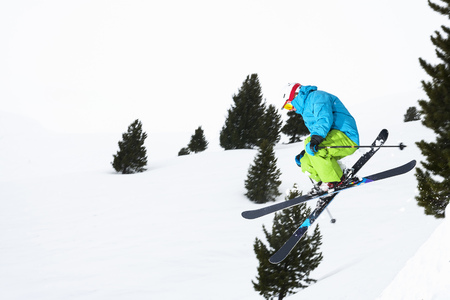 Skier jumping on snowy slope LANG_EVOIMAGES