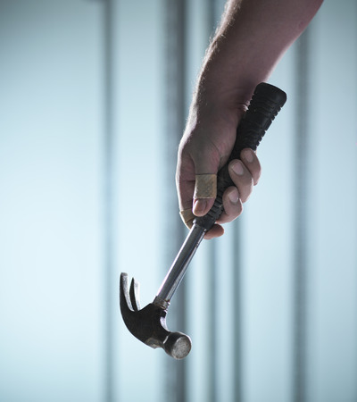 claw hammer: Close up of hand holding hammer LANG_EVOIMAGES