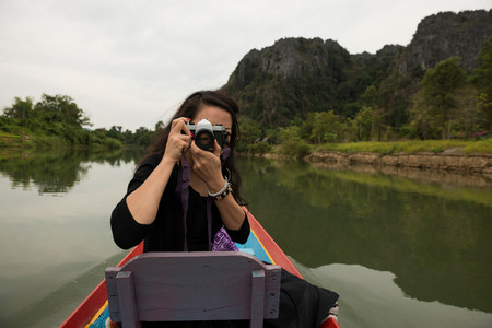 pastoral scenery: Woman taking photograph on boat on Nam Song River,Vang Vieng,Laos